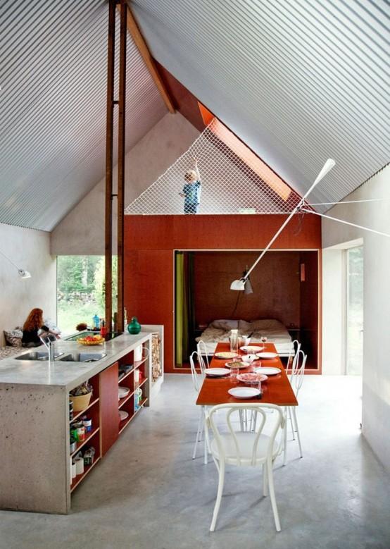 una cucina industriale incontra l'isola contemporanea di cemento e sequoia, con lavelli e molto spazio di archiviazione aperto