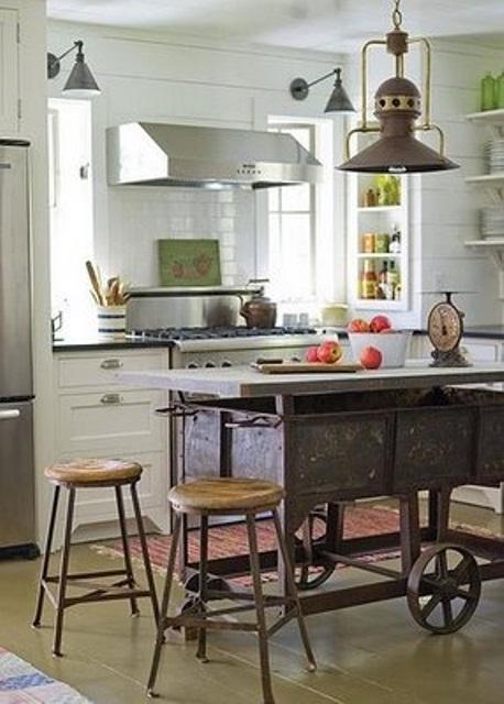 un unico carro vintage in metallo su ruote usato come isola da cucina, un paio di sgabelli e una lampada a sospensione