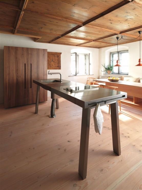 un'isola cucina contemporanea in legno e metallo progettata come un tavolo per sembrare più leggera, con un lavandino e alcuni supporti