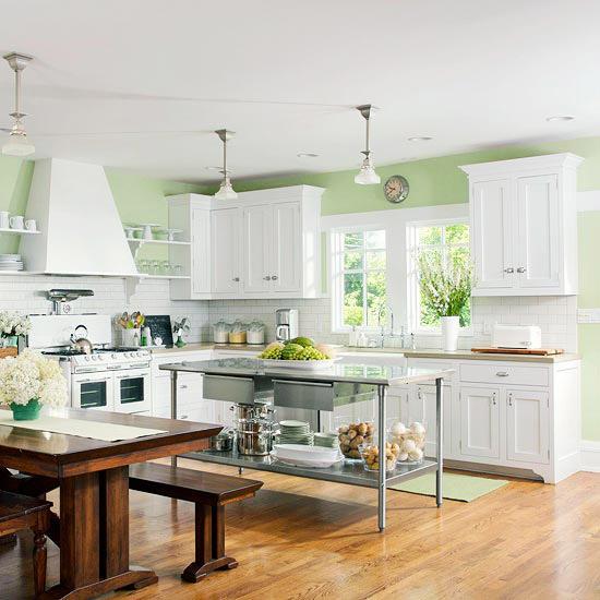 una semplice isola da cucina in metallo con un ripiano aperto contrasta con la tradizionale cucina bianca e un set da pranzo in legno tinto scuro dark