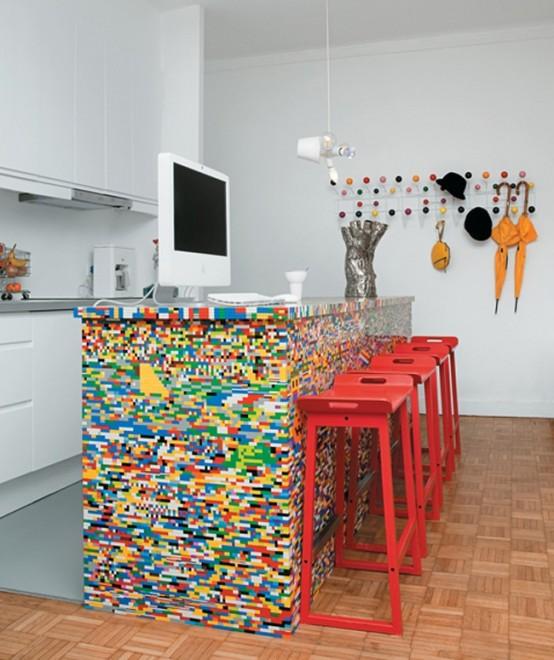 un'isola della cucina Lego colorata e sgabelli rosso vivo fanno una dichiarazione nella cucina neutra e lo abbelliscono