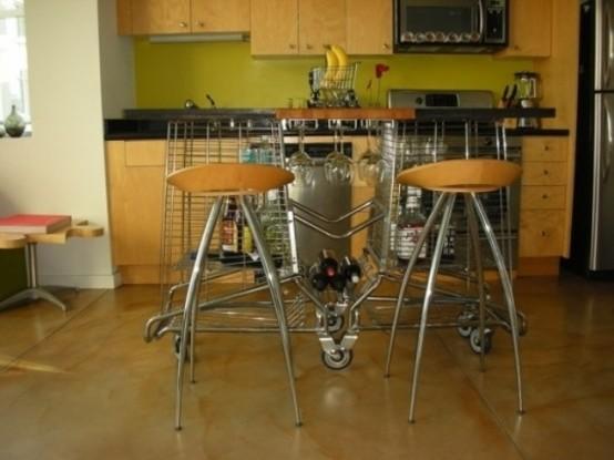 una strana isola da cucina in metallo su rotelle e con un piano in legno contrasta con la cucina semplice e moderna in compensato