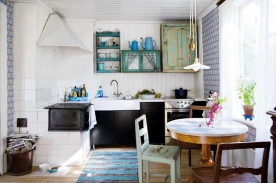un moderno incontra la cucina scandinava vintage con armadi neri, un tavolo rotondo, sedie spaiate e armadi shabby chic dai colori vivaci