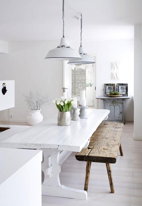 una cucina scandinava bianco puro con un tavolo rustico bianco, una panca in legno grezzo e un armadio azzurro con foto