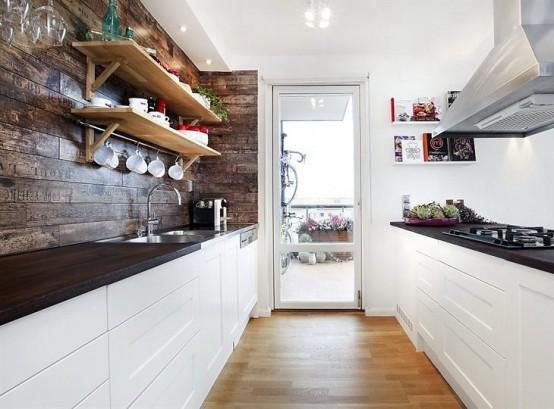 un contemporaneo incontra la cucina rustica con armadi bianchi e controsoffitti scuri e ricco legno tinto sul muro più scaffali aperti