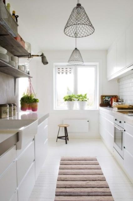 una moderna cucina scandinava bianca con eleganti armadietti, lampade a sospensione in rete e un tappeto a righe