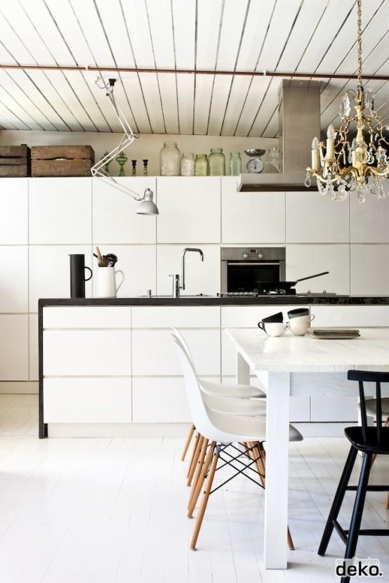 una cucina nordica bianco sporco con un soffitto in legno, eleganti armadi bianchi e un piano di lavoro nero, un lampadario vintage e sedie bianche su gambe di legno