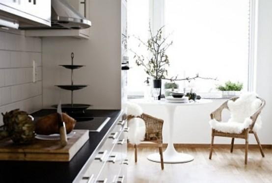 un'accogliente cucina monocromatica, un piano di lavoro nero, sedie in vimini, eco-pelliccia e un tavolo rotondo