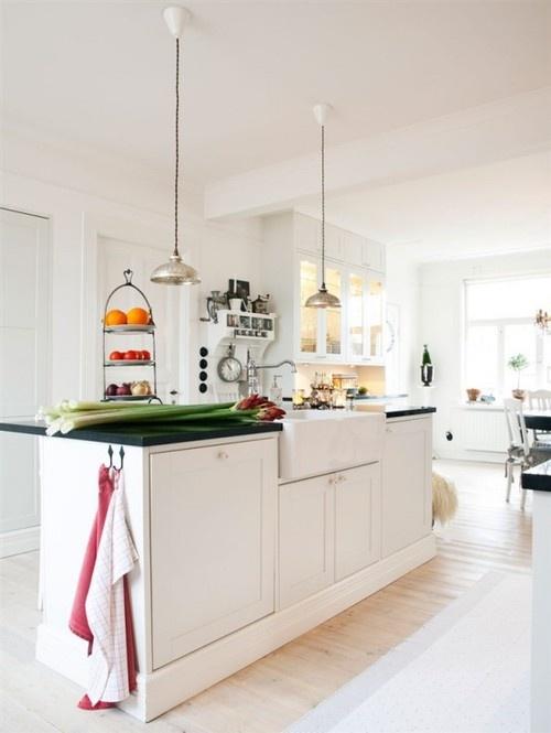 una moderna cucina scandinava bianca con una grande isola cucina con piano di lavoro nero, lampade a sospensione e un buffet di vetro