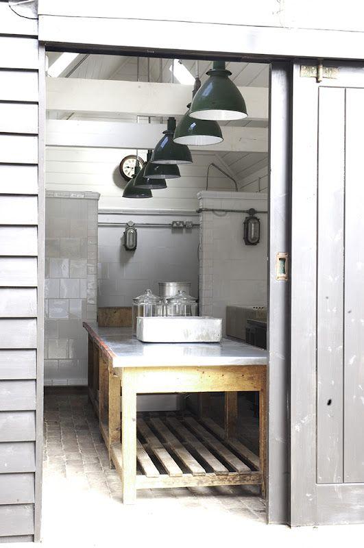 una cucina scandinava neutra realizzata con piastrelle bianche, un'isola da cucina in legno e metallo e lampade a sospensione scure
