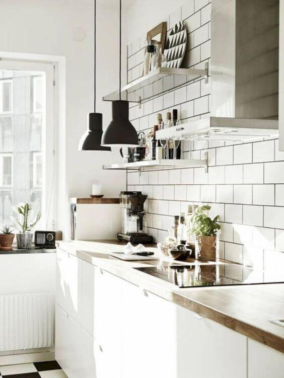 una cucina ariosa con piastrelle bianche, armadi bianchi, ripiani in legno, lampade a sospensione nere