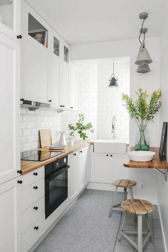 una piccola cucina nordica con armadi bianchi, hardware nero, controsoffitti butcherblock e piastrelle bianche più sgabelli in legno e metallo