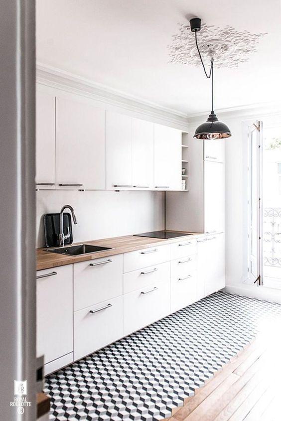 un'ariosa cucina scandinava con armadi bianchi, controsoffitti butcherblock, un pavimento geometrico e lampade a sospensione