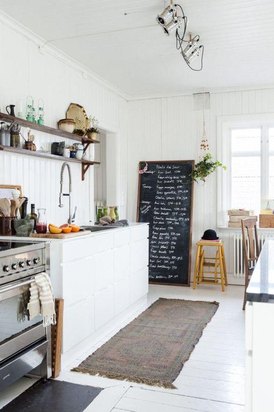 un'accogliente e luminosa cucina nordica con pareti a travi, pavimento bianco, lavagna ed eleganti armadietti più luci