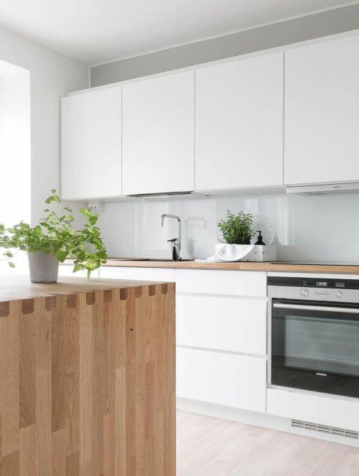 un'elegante cucina nordica con armadi bianchi, un paraschizzi in vetro blu, un'isola da cucina in legno tinto chiaro