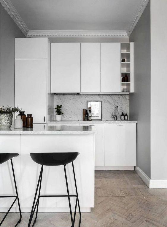 una piccola cucina nordica con eleganti armadi bianchi e un ripiano in pietra grigia e blacksplash più sgabelli neri