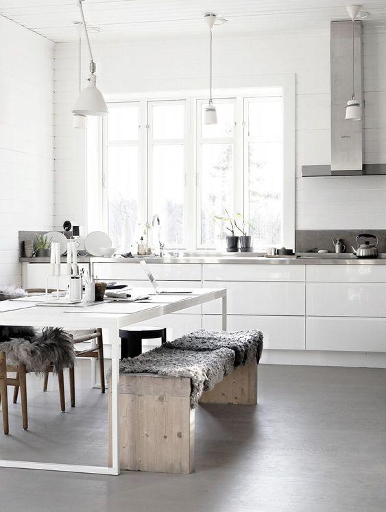 una cucina nordica neutra con eleganti armadi bianchi, ripiani in metallo, un tavolo bianco e panche in legno più lampade a sospensione