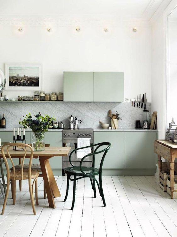 una cucina nordica con armadi verdi, ripiani in pietra bianca e un paraschizzi, un tavolo in legno e sedie vintage