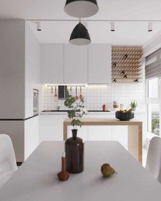 una cucina bianca minimalista con luci integrate, un portabottiglie di vino, un'isola da cucina in legno minimale e un set da pranzo bianco