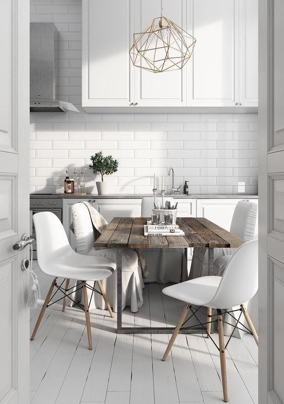 una cucina nordica con ante e piastrelle bianche, un tavolo in legno grezzo, moderne chais bianche e un lampadario geometrico