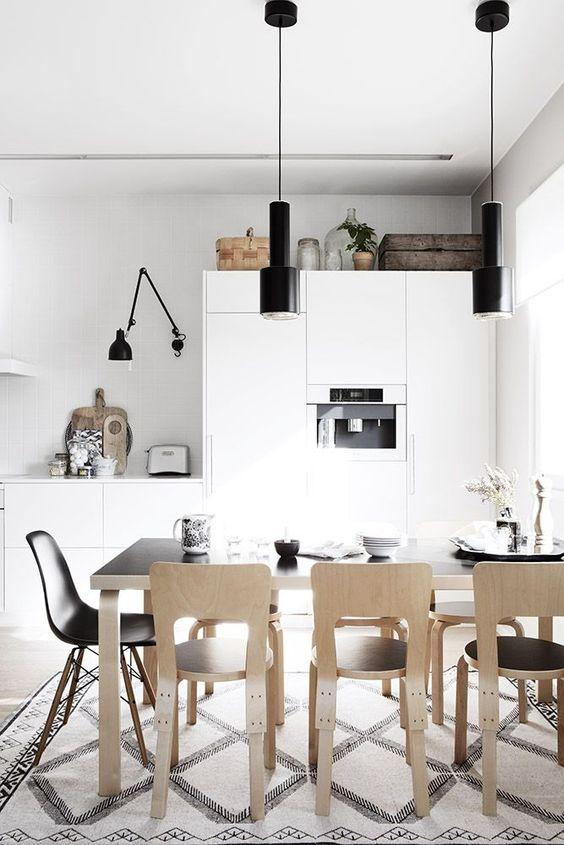 una cucina nordica con eleganti armadi bianchi, lampade nere, un tavolo nero e sedie in compensato