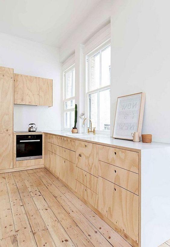 una semplice cucina scandinava neutra con armadi in compensato, ripiani bianchi e pavimento in legno