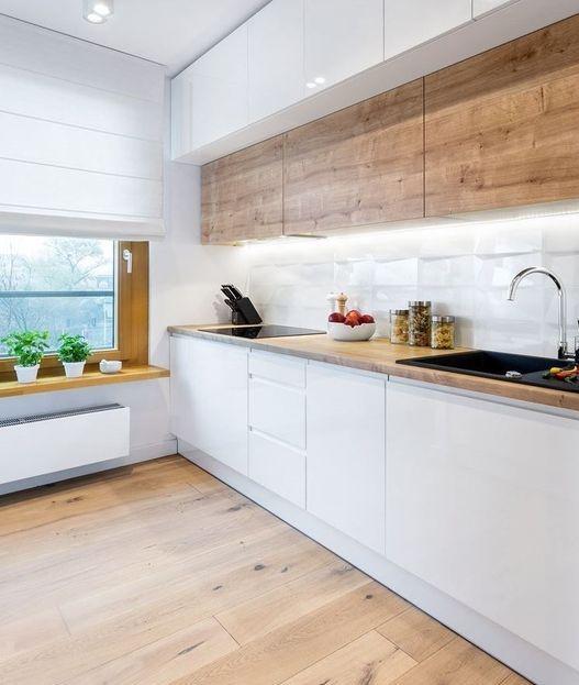 una cucina scandinava minimalista con pensili superiori in legno, eleganti inferiori bianchi, un ripiano sul davanzale e luci integrate