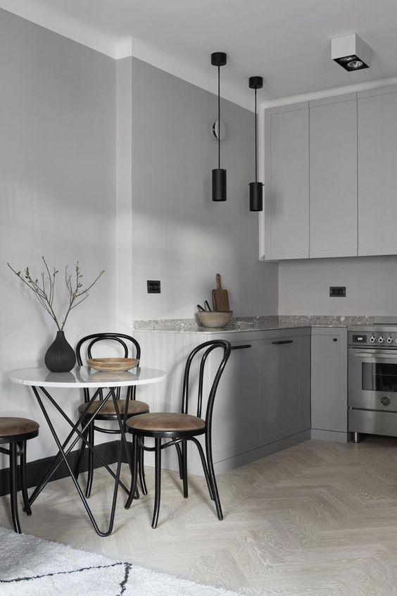 una cucina nordica minimalista grigia con lampade a sospensione nere, un piano di lavoro in pietra grigia e un tavolo con gambe a forcina