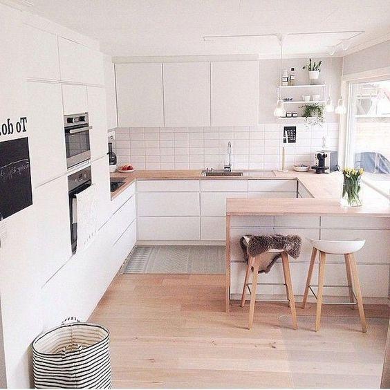 una cucina scandinava minimalista con eleganti armadi bianchi, piani di lavoro leggeri, sgabelli ed elettrodomestici da incasso