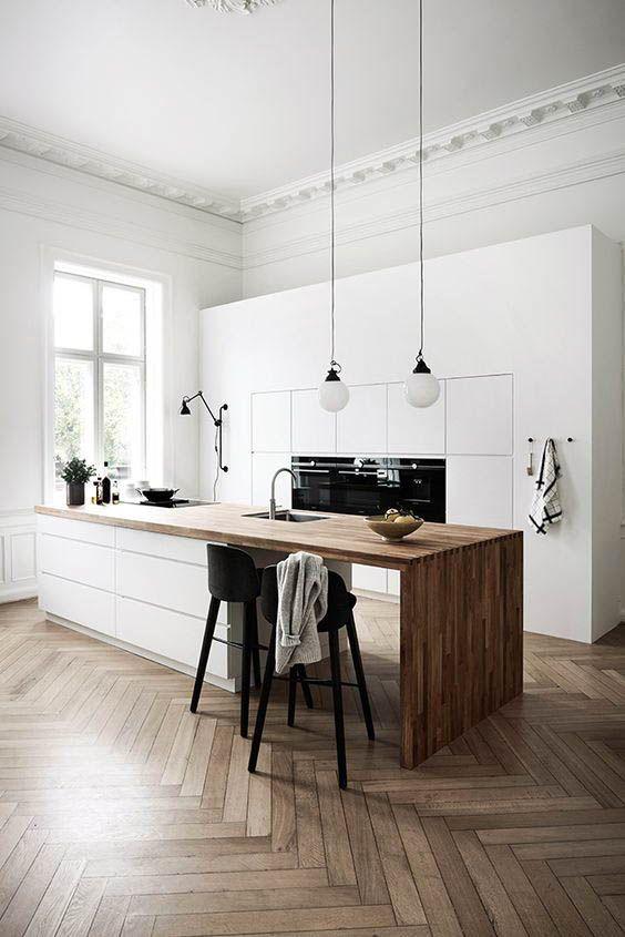 una cucina nordica minimalista con eleganti armadi bianchi, un'isola cucina bianca elegante con un controsoffitto a cascata in legno e lampade a sospensione