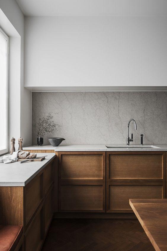 una cucina scandinava minimalista con eleganti tomaie bianche, armadietti inferiori in legno con pannelli, un paraschizzi in pietra e controsoffitti