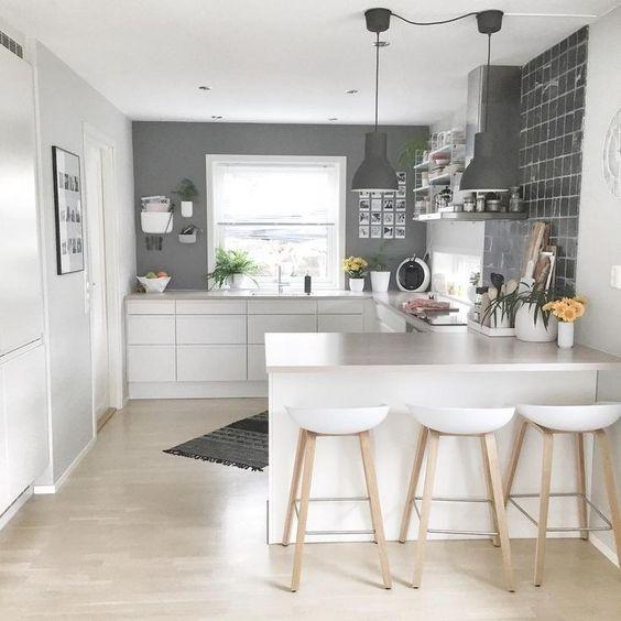 una cucina minimalista Scandi con pareti grigie, eleganti armadi bianchi, sgabelli e lampade a sospensione