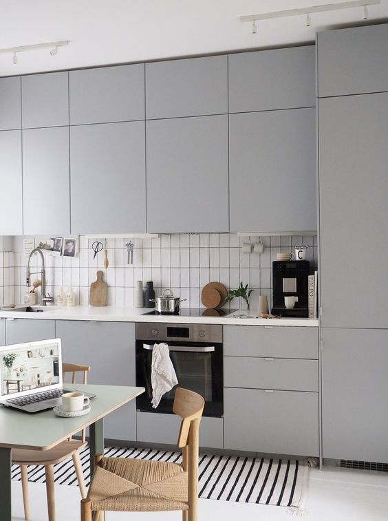 una cucina grigia minimalista, piastrelle bianche, sedie intrecciate e un tavolo da pranzo semplice e piccolo