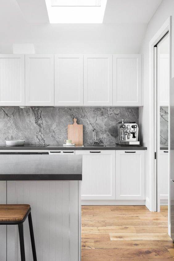 una cucina nordica minimale con armadi a pannelli bianchi, un paraschizzi in pietra grigia, ripiani neri e un pavimento in legno