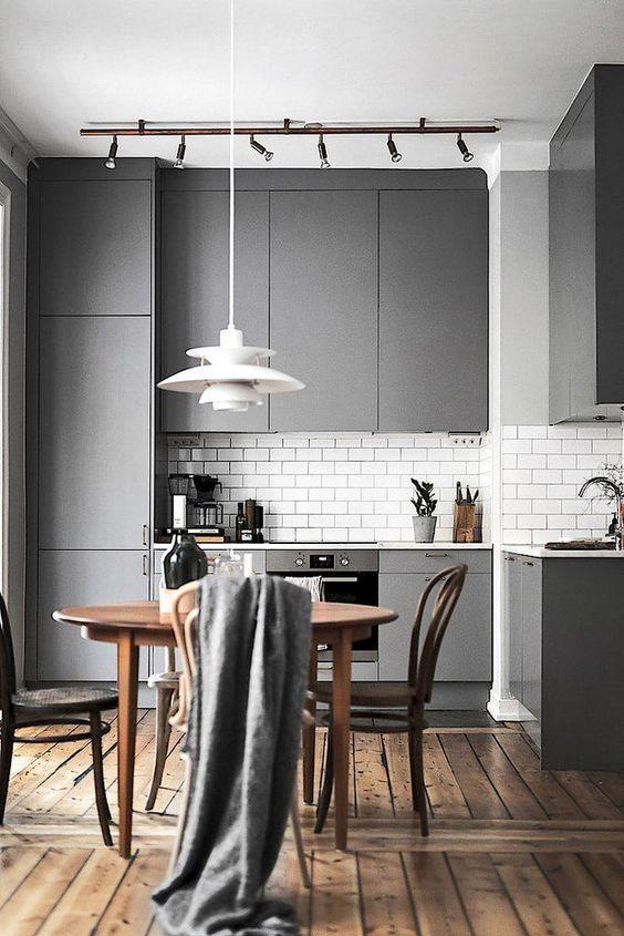 una cucina minimalista laconica con eleganti armadi grigi, un set da pranzo in legno, una lampada a sospensione e luci aggiuntive