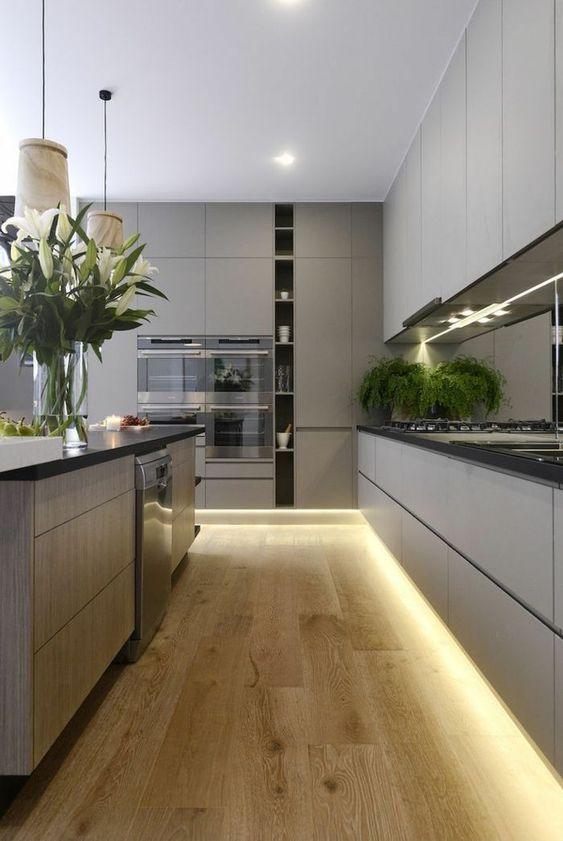 una cucina minimalista grigia con mobili eleganti, ripiani neri, luci integrate e lampade a sospensione