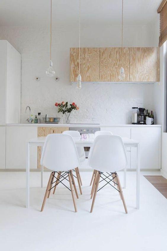 una cucina scandinava contemporanea con armadi bianchi e compensato, lampadine appese dall'alto e un elegante set da pranzo