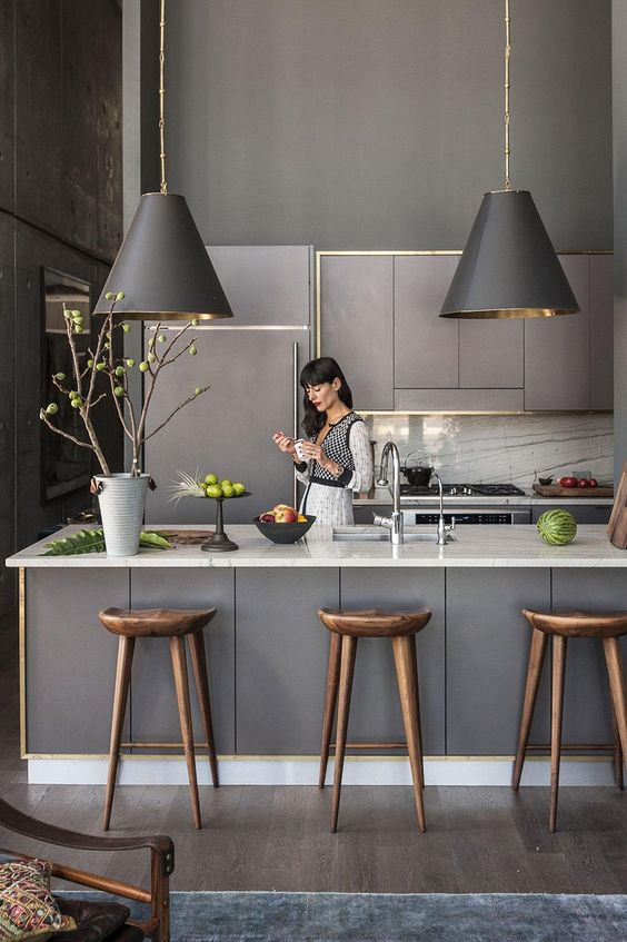 una cucina scandinava grigia con eleganti armadi illuminati, lampade a sospensione, ripiani in pietra bianca e un paraschizzi