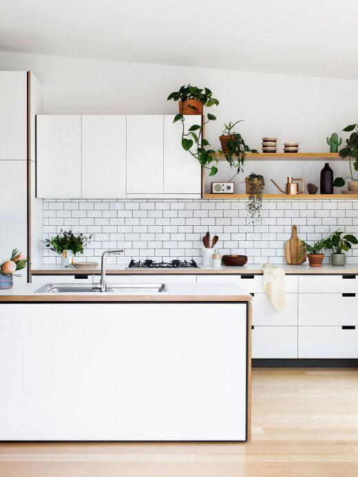 una cucina nordica bianca contemporanea con armadi eleganti, ripiani in legno, piante in vaso e un paraschizzi in piastrelle bianche della metropolitana