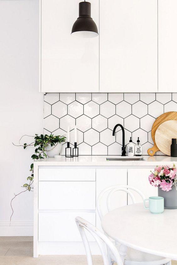 una cucina bianca contemporanea con mobili eleganti, piastrelle esagonali con stucco nero, hardware nero e fioriture
