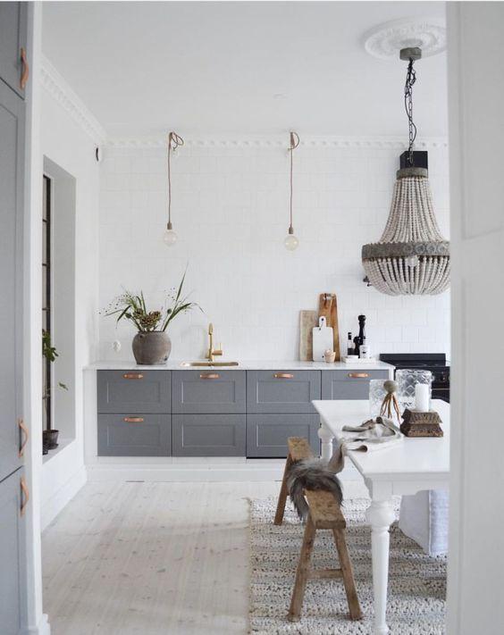un contemporaneo incontra la cucina vintage con armadi grigi, lampade a sospensione e un lampadario, un tavolo e panche vintage bianchi