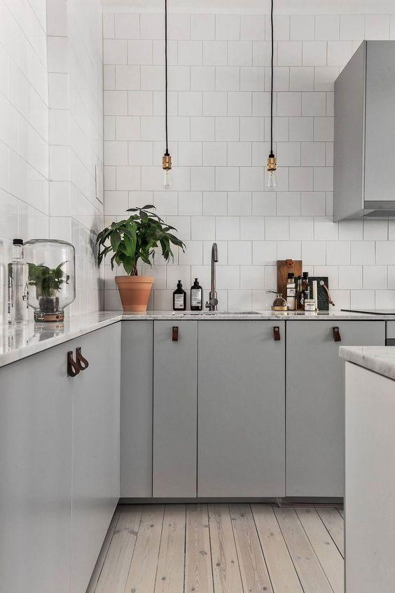 una cucina scandinava contemporanea con pensili grigi con maniglie in pelle, lampadine, piastrelle bianche e pavimento in legno