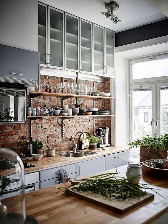 un'elegante cucina scandinava con un muro di mattoni, scabinet in vetro grigio e smerigliato, controsoffitti butcherblock e molta luce
