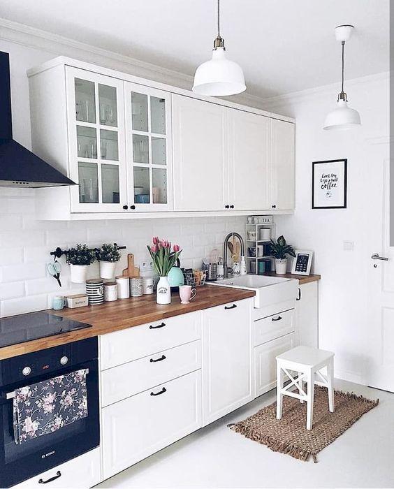 una cucina Scandi bianca con armadietti di ispirazione vintage e hardware nero, controsoffitti butcherblock e lampade a sospensione