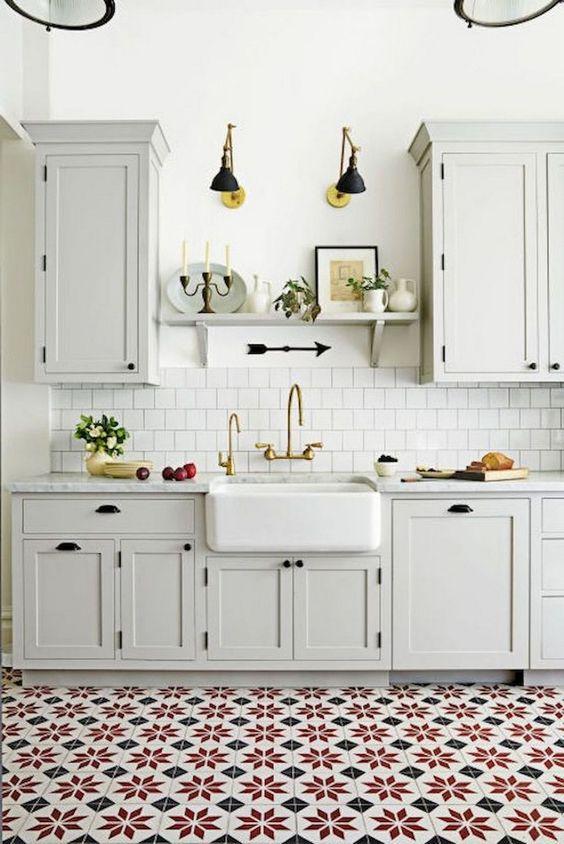 una cucina vintage neutra con armadi eleganti, un paraschizzi di piastrelle bianche, un pavimento di piastrelle colorate e lampade da parete nere