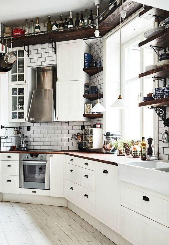 una cucina nordica di ispirazione vintage con mensola a soffitto, piastrelle bianche, armadietti vintage bianchi e piani di lavoro riccamente colorati