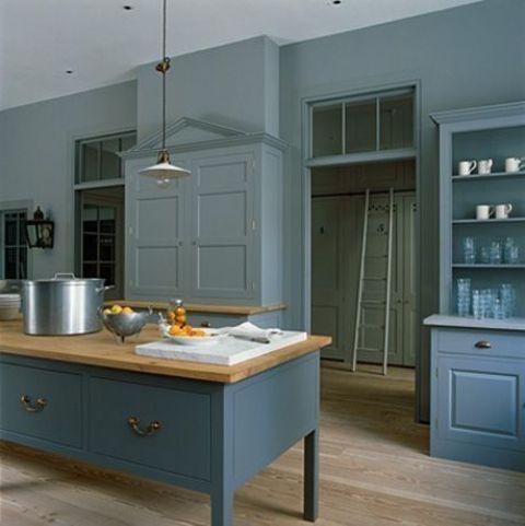 una cucina vintage blu con armadi a pannelli, ripiani in legno e lampade a sospensione