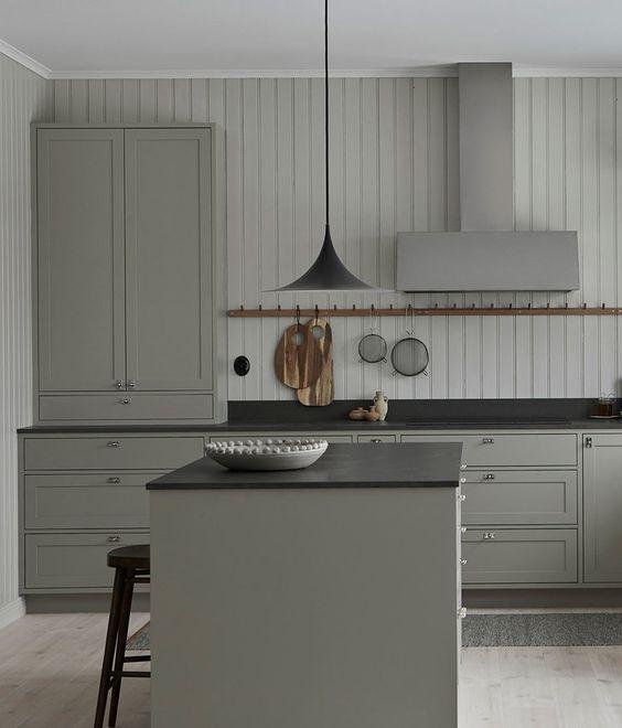 una cucina vintage grigia con eleganti armadi, ripiani neri, una lampada a sospensione nera e una parete shiplap