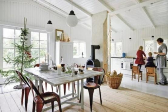 una cucina scandinava bianca con un tavolo imbiancato, armadi bianchi, un camino e lampade a sospensione