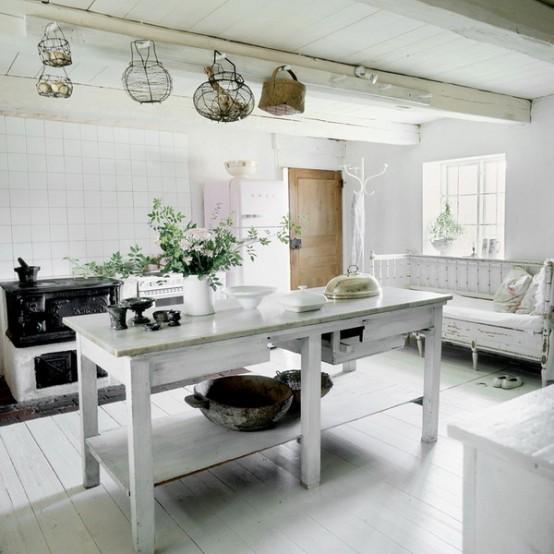 una cucina scandinava bianca con un tocco vintage, un'isola e una panca imbiancate a calce, armadi bianchi e una stufa vintage